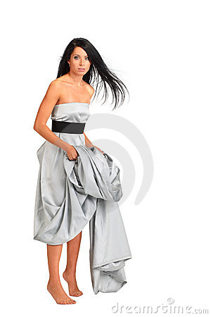 Woman wearing long silver dress stands on tiptoe
