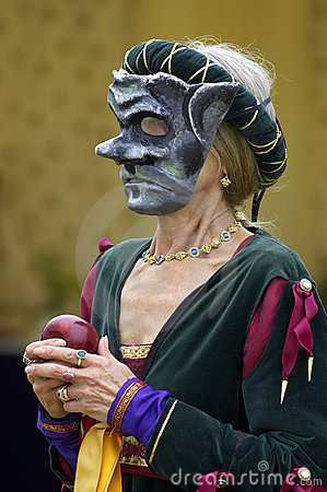 Woman wearing a mediaeval mask while holding a red apple