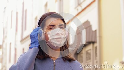 Woman wearing medical mask and gloves in city stock footage