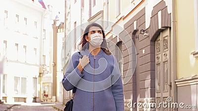 Woman wearing medical mask walking in city stock video