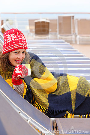 Woman wearing in mittens and plaid lies on lounger