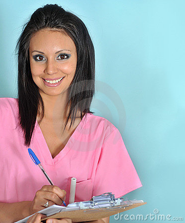 Woman wearing pink scrubs holding clip board
