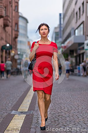 Free Woman Wearing Red Dress And Walking Along Road Royalty Free Stock Photo - 123041435