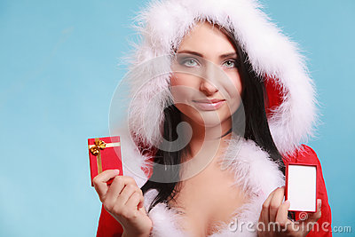 Woman wearing santa claus costume holds gift box on blue stock photo