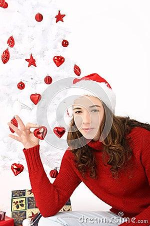 Woman wearing santa hat holding an heart