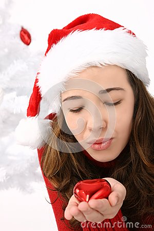 Woman wearing santa hat holding an heart