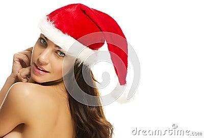 Woman wearing santas hat looking over her shoulder