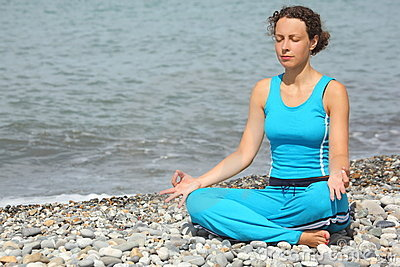Woman wearing sporty clothers is meditate on sea