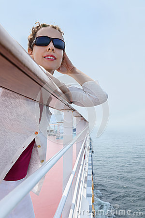 Woman wearing sunglasses stands on board of ship