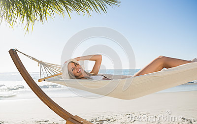 Woman wearing sunhat and bikini relaxing on hammock smiling at camera