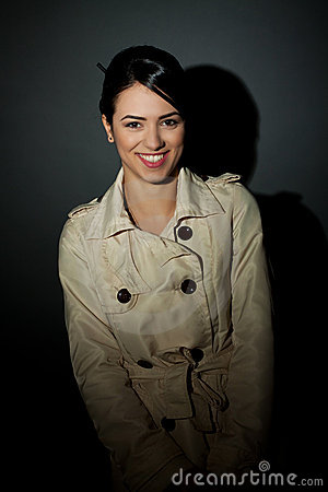 Woman wearing a trench coat and smiling