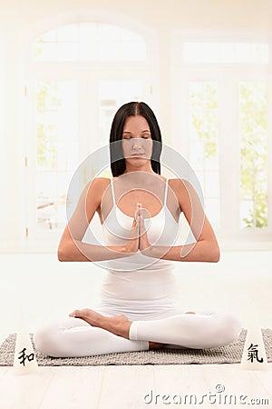 Woman wearing white doing yoga exercise