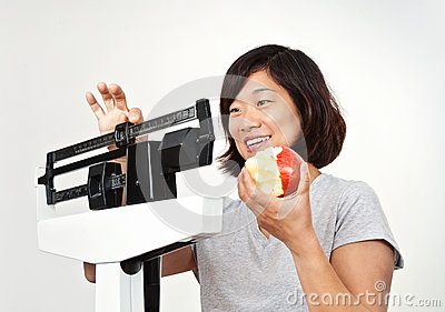Woman on Weight Scale Pleased with Her Weight Loss