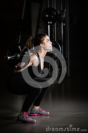 Woman weight training at gym.Devoted body builder girl lifting weights in gym and doing squats low key photo Stock Photo