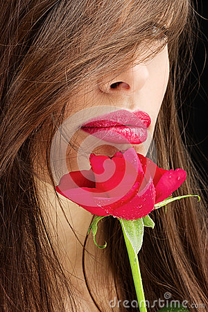 Woman and wet red rose near her lips