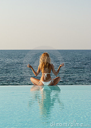 Woman in white bikini meditating on infinity pool