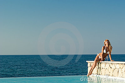 Woman in white bikini sitting on the edge of pool