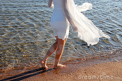 Woman in white dress back walking on beach