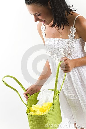 Woman in white dress looking inside shopping bag