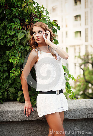 Woman in white dress talking on mobile phone