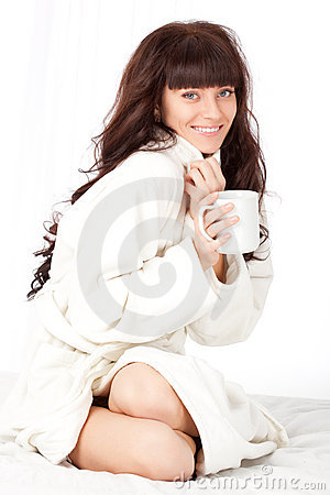 Woman with white mug wearing dressing gown