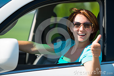 Woman in white new car at nature with thumbs up sign