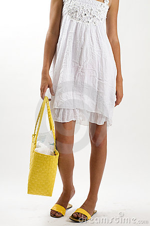Woman in white summer dress with yellow bag
