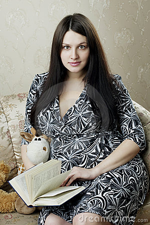 Woman, who reads book sitting on the sofa