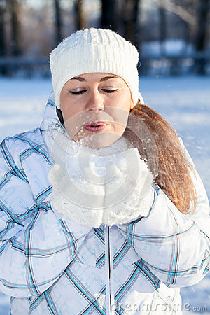 Female in winter clothes blowing at snow in mittens