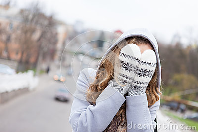 Woman in winter clothes covered face with mittens