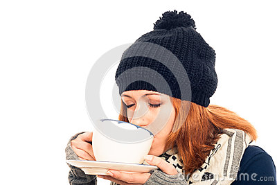 Woman in winter clothes drinking hot drink