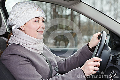 Woman in winter clothes driving car