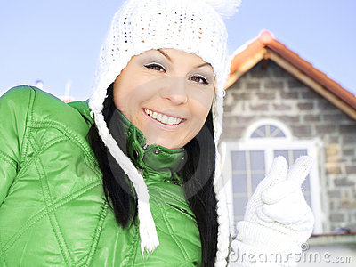 Woman in winter clothes pointing new house