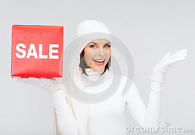 Woman in winter clothes with red sale sign