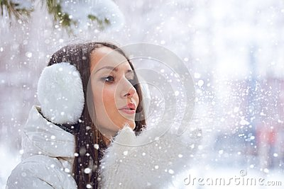 Woman in winter park blowing on snow