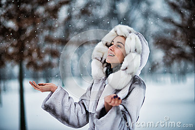 Woman in winter park have fun with a snow