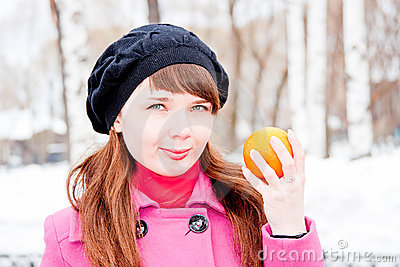 Woman in winter in a park with orange in hands