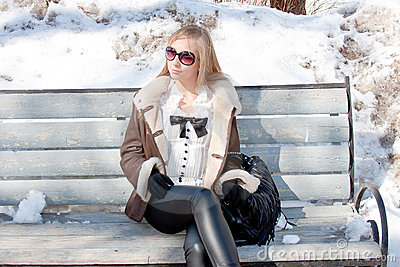 Woman in a winter park sits on a bench