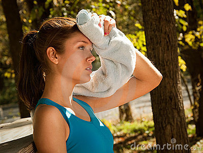 Woman wiping brow with towel