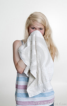 Woman wiping her face with towel
