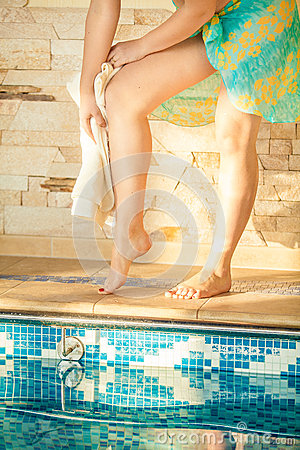 Woman wiping legs with towel after swimming pool