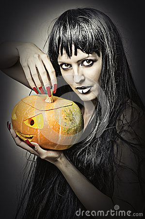 Woman witch holding pumpkin