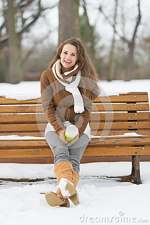Free Woman With Cup Of Hot Beverage Sitting On Bench In Winter Park Royalty Free Stock Images - 33961729