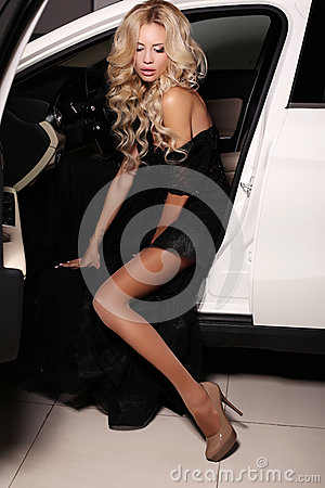 Free Woman With Long Blond Hair Wears Luxurious Dress,posing In White Car Stock Image - 62984901