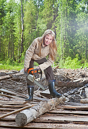 Woman in wood saws a tree a chain saw