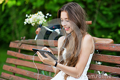 Woman on wooden bench with digital tablet