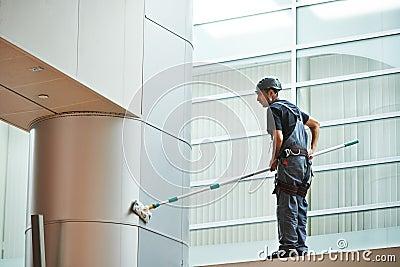 Woman worker cleaning indoor window