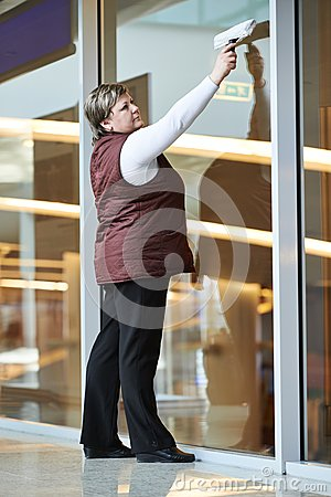 Woman worker cleaning indoor window