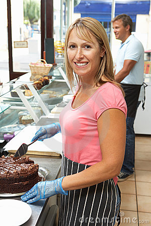 Woman Working Behind Counter In Cafe Slicing Cake