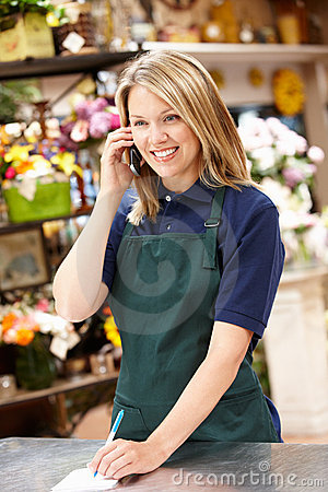 Woman working in florist on phone
